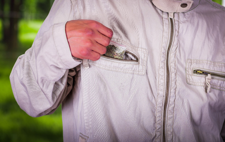Close up of a man dealer saving in the pocket of his jacket drug, trafficking, crime, in a blurred background Stock Photo