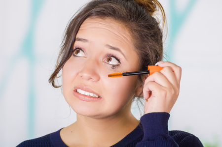 Close up of worried young woman doing a mess using a eye mascara in her eye, in a blurred background