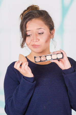 Close up of worried young woman holding a make up palette and doing crazy make-up in her face using a sponge, in a blurred background