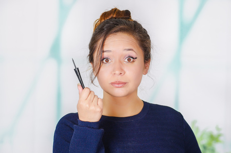 Close up of beautiful young woman holding a eyeliner in her hand, in a blurred background