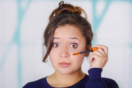Close up of surprised young woman doing a mess using a eye mascara in her eye, in a blurred background