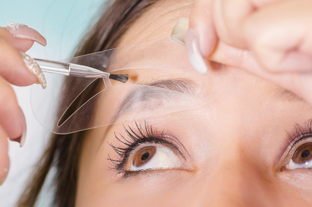 Close up of young beautiful woman doing a mess in her eyebrow in a blurred background Stock Photo