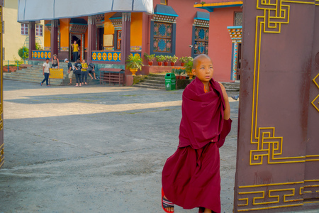 POKHARA, NEPAL - OCTOBER 06 2017: Unidentified Buddhist monk boy walking close to a door at the Tashi refugee settlement in Pokhara, Nepal Editorial