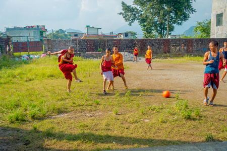 POKHARA, NEPAL - OCTOBER 06 2017: Unidentified Buddhist monk teenager playing soccer at the Sakya Tangyud monastery in the Spiti valley in Pokhara, Nepal Editorial
