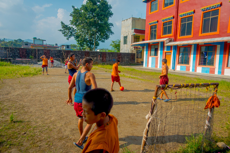POKHARA, NEPAL - OCTOBER 06 2017: Unidentified group of Buddhist monk teenagers playing soccer at outdoors of the Sakya Tangyud monastery in the Spiti valley in Pokhara, Nepal Editorial