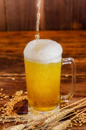 Close up of a glass of light beer with foam, with a wheat branch and wheat on a wooden table in a blurred background