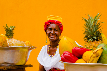 Portrait of woman in traditional costume with a basket of fruits, in a yellow background of Cartagena de Indias, Colombia