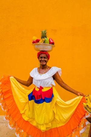 Schließen Sie oben von der Frau im traditionellen Kostüm mit einem Korb von Früchten in ihrem Kopf in einem gelben Hintergrund von Cartagena de Indias, Kolumbien
