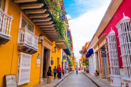 CARTAGENA, KOLUMBIEN 22, 2017: Nicht identifizierte Leute, die Fotos in Cartagena-Stadtstraße mit buntem Gebäude von Cartagena ummauerten Stadt gehen und machen Editorial