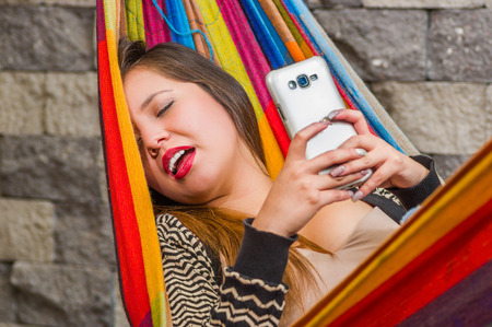 Close up of young beautiful woman sleeping in a hammock with her mouth open, while she is with a cellphone in her hands, in blurred background