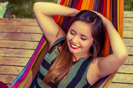 Above view of smiling young beautiful woman relaxing in a hammock with both arms behind her head, in wooden background