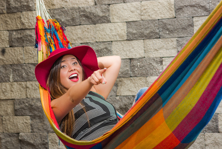 Close up of young beautiful woman wearing a red fashion hat and relaxing in a hammock, pointing somewhere with her arm, in blurred background