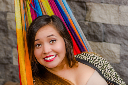 Portrit of young smiling woman lying in a hammock in garden in a blurred background