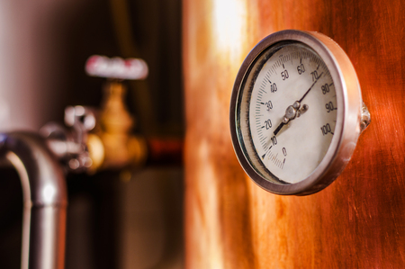 Close up of a pressure gauge inside of a modern beer plant brewery with vessels, tubs and pipes made of stainless steel, in a beer plant in Quito