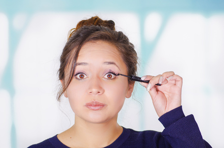 Close up of beautiful young woman holding a eyeliner and doing crazy make-up in her face, in a blurred background Stock Photo