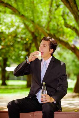 Handsome young businessman wearing a suit and eating a sandwich and holding a bottle of water with his other hand at outdoors, in a blurred park background