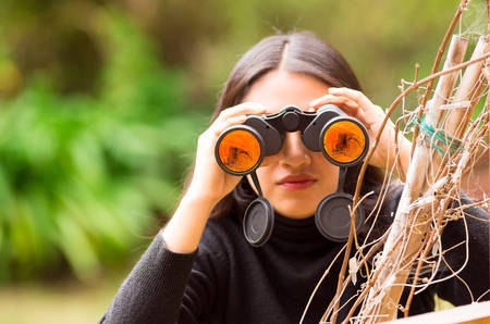 Young woman looking through black binoculars in the forest in a blurred background