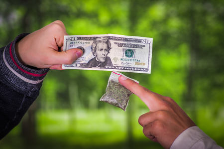Close up of a man addict and dealer trafficking, addict with money buying dose from dealer with drugs, in a blurred background