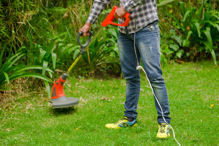 Young worker wearing jeans and long sleeve shirt and using a lawn trimmer mower cutting grass in a blurred nature background Banque d'images