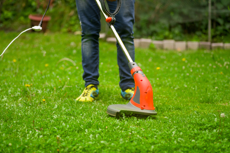 Close up of young worker with a string lawn trimmer mower cutting grass in a blurred nature background Foto de archivo