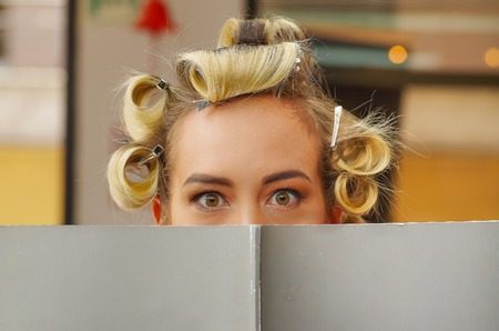 Portrait of blonde woman hiding behind a book with curlers in the head, in a hair salon background Stock Photo