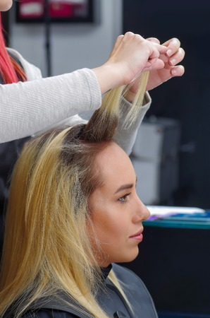 Close up of a beautiful woman in a hair salon and hair stylist drying blond hair with hair dryer and round brush in a blurred background
