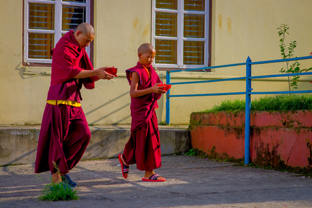 POKHARA, NEPAL - OCTOBER 06 2017: Unidentified Buddhist monk teenarger holding in their hands a red bowl and walking at outdoors at the Tashi refugee settlement in Pokhara, Nepal Editorial