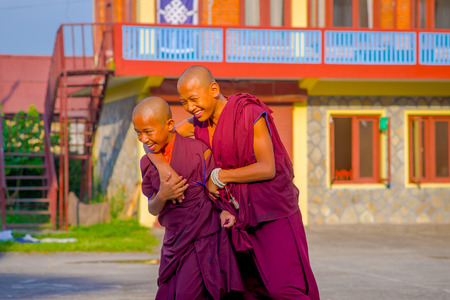 POKHARA, NEPAL - OCTOBER 06 2017: Smiling brothers Buddhist monk boys hugging each other at outside at the Tashi refugee settlement in Pokhara, Nepal