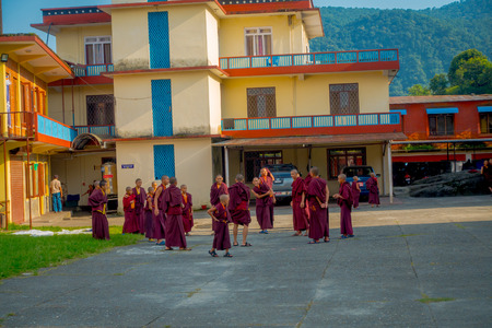 POKHARA, NEPAL - OCTOBER 06 2017: Outdoor view of unidentified Buddhist monk teenagers enjoying the free time in a patio and playing with their friends at the Tashi refugee settlement in Pokhara, Nepal