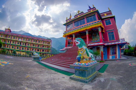 POKHARA, NEPAL - OCTOBER 06 2017: Tibet architecture. with a stoned lion at the enter of Sakya monastery is a pilgrim and tourist destination. Its religious structure is influenced by Mongol style, fish eye effect