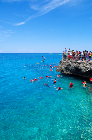 WEST VIEW, COLOMBIA - OCTOBER 03, 2017: Outdoor view of unidentified people jumping from a rock, swimming and enjoying the beautiful view in a gorgeous blue water, San Andres Island from Johnny Cay during a sunny day in San Andres, Colombia