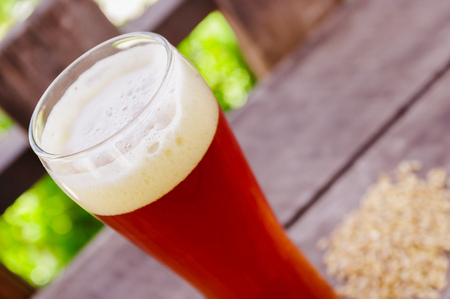 Close up of glass of beer with a blurred nature background