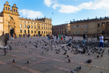BOGOTA, COLOMBIA OCTOBER 22, 2017: Unidentified people walking in Bolivar square in a beautiful blue sky with dozens of pigeons in the square, in Bogota, Colombia, Latin America Editorial