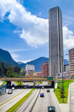 BOGOTA, COLOMBIA - OCTOBER, 22, 2017: Beautiful outdoor view of the Colpatria Tower, Transmilenio with some cars in the highway in Bogota