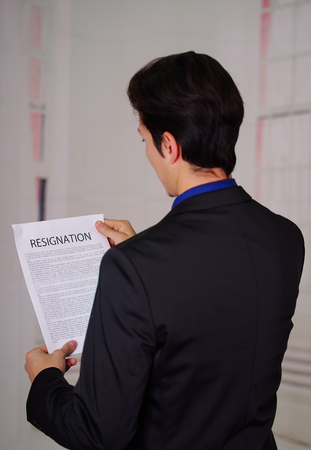 Close up of businessman wearing a suit and holding a sheet of paper of resignation text on it, in a blurred background, giving a back