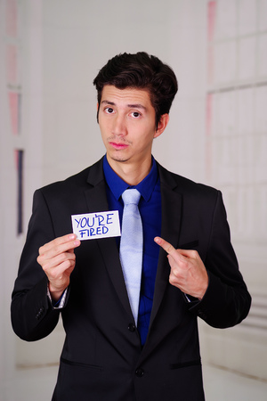 Sad business man holding a paper of youre fired text on it, in a blurred background
