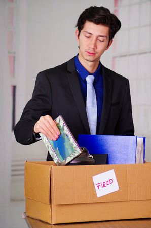 Close up of sad man packing his belongings after being fired from his job in a blurred background Stock Photo