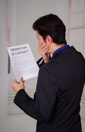 Close up of surprised businessman wearing a suit and holding a paper of termination of contract text on it, in a blurred background giving a back