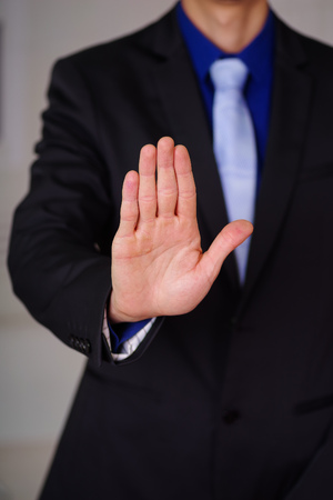Close up of man wearing a suit with his open hand pointing in front of him, in a blurred background