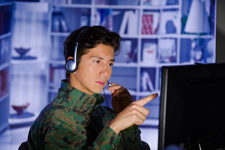 Portrait of handsome young soldier wearing a military uniform, military drone operator watching at his computer and using his headphone to give an advice and pointing with his finger the screen