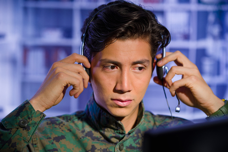 Portrait of handsome soldier wearing a military uniform, watching at his computer and fixing his headphones around the head, ready to give an advice, in a blurred background