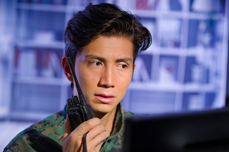 Portrait of worried young soldier wearing a military uniform, military drone operator watching at his computer and using a radio to give an advice