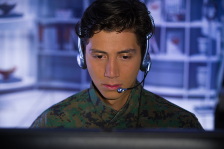 Portrait of young soldier wearing a military uniform, military drone operator watching at his computer and talking through his headphones to give an advice Stock Photo