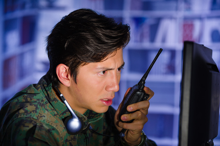 Portrait of young soldier wearing a military uniform, military drone operator watching at his computer and using a radio to give an advice, with headphones around his neck