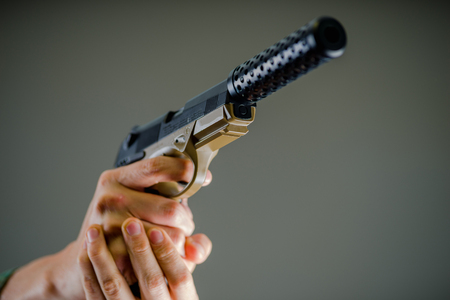 Close up of a soldier holding with both hands a heavy gun in gray background Stock Photo