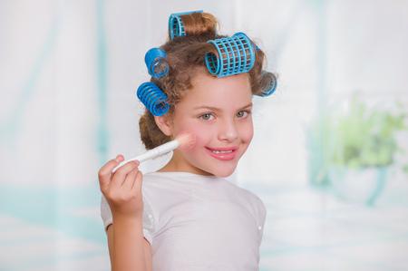 Mała piękna dziewczyna za pomocą pędzla do makijażu podczas noszenia wałków do włosów i szlafrok na niewyraźne tło Zdjęcie Seryjne