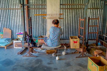 POKHARA, NEPAL - OCTOBER 06 2017: Unidentified woman working on loom manufacturing wool shawl clothing in Nepal Standard-Bild - 95942465