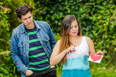 Close up of young woman with a disgusting face holding in her hands a letter, with a worried boyfriend looking his girlfriend, friend zone concept
