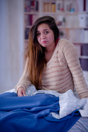 Young woman with sleeplessness sitting on the bed, insomnia concept Stock Photo