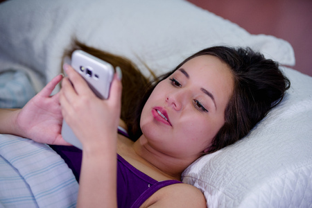 Portrait of a young woman suffering from insomnia and using her cellphone in bed Stock Photo